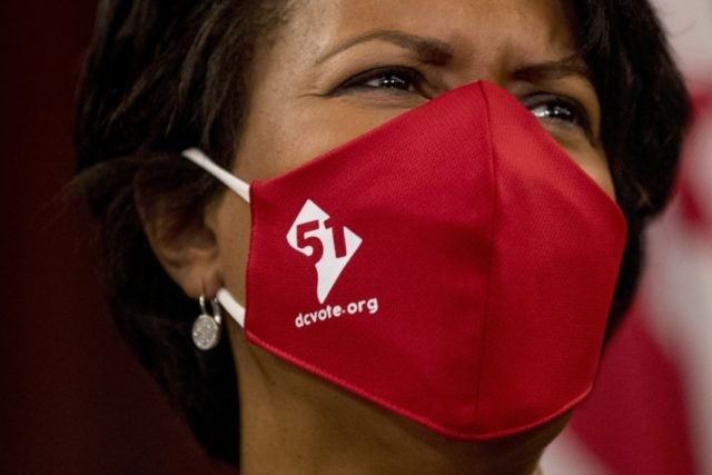In this June 16, 2020, file photo District of Columbia Mayor Muriel Bowser wears a mask with the number 51 over a map of the District of Columbia during a news conference on D.C. statehood on Capitol Hill in Washington. Bowser must pull off a public juggling act as the …