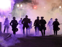 In this March 29, 2020, file photo, police officers walk enveloped by tear gas in Portland, Ore. City commissioners in Portland voted Wednesday, June 17, 2020 to cut nearly $16 million from the Portland Police Bureau's budget in response to concerns about police brutality and racial injustice. The cuts are …