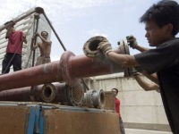 Chinese workers loading steel pipes onto a truck in Beijing, China, Tuesday, Aug 1, 2006. China is the world's biggest consumer of steel, grain, aluminum, cement, copper, iron ore and zinc, among other commodities. China's resource rush has helped fuel three years of robust global economic growth and contributed to …