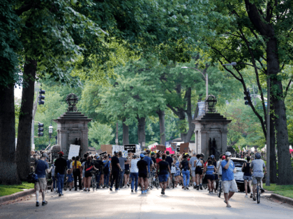 Protesters walk through the gate of a private street not far from the home of Mark and Patricia McCloskey, Friday, July 3, 2020, in St. Louis. Mark and Patricia McCloskey were seen on June 28, 2020, standing outside their mansion with guns drawn confronting passing protesters. The protesters passed by …