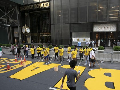 Volunteers paint Black Lives Matter on Fifth Avenue in front of Trump Tower, Thursday, July 9, 2020, in New York. (AP Photo/Mark Lennihan)
