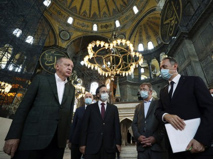 Turkey's President Recep Tayyip Erdogan, left, listens to an official as he visits the Byzantine-era Hagia Sophia, one of Istanbul's main tourist attractions in the historic Sultanahmet district of Istanbul, Sunday, July 19, 2020, days after he formally reconverted Hagia Sophia into a mosque and declared it open for Muslim …