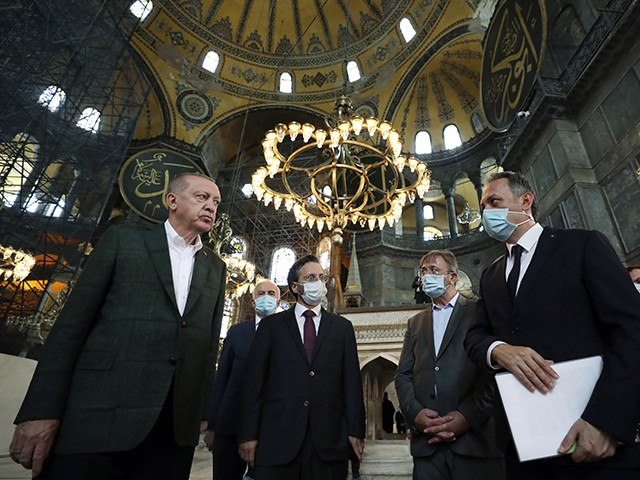 Turkey's President Recep Tayyip Erdogan, left, listens to an official as he visits the Byzantine-era Hagia Sophia, one of Istanbul's main tourist attractions in the historic Sultanahmet district of Istanbul, Sunday, July 19, 2020, days after he formally reconverted Hagia Sophia into a mosque and declared it open for Muslim worship, after a high court annulled a 1934 decision that had made the religious landmark a museum.(Turkish Presidency via AP, Pool)