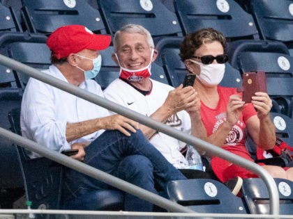 Dr. Anthony Fauci, director of the National Institute of Allergy and Infectious Diseases, center, smiles as he watches an opening day baseball game between the Washington Nationals and the New York Yankees at Nationals Park, Thursday, July 23, 2020, in Washington. (AP Photo/Alex Brandon)