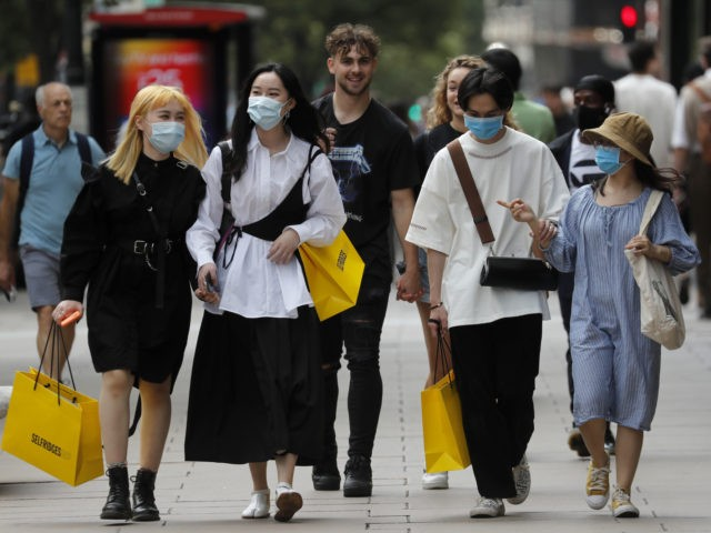 Shoppers wear face coverings to protect themselves from COVID-19 as they walk along Oxford Street in London, Friday, July 24, 2020. New rules on wearing masks in England have come into force, with people going to shops, banks and supermarkets now required to wear face coverings. Police can hand out …