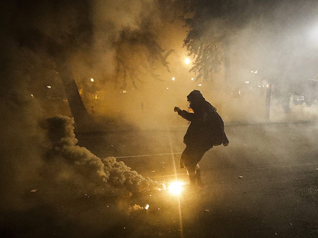 A demonstrator kicks back a tear gas canister back at federal officers during a Black Lives Matter protest at the Mark O. Hatfield United States Courthouse Wednesday, July 29, 2020, in Portland, Ore. (AP Photo/Marcio Jose Sanchez)