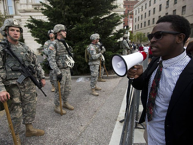 A protester talks with National Guard soldiers during a protest through Baltimore, Maryland on April 29, 2015, demanding justice for an African-American man who died of severe spinal injuries sustained in police custody. His death was the latest instance in the United States of a black man succumbing at the …