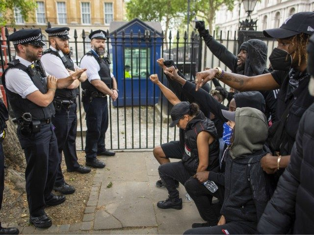 LONDON, ENGLAND - JUNE 03: People kneel in front of police during a Black Lives Matter protest at Hyde Park on June 03, 2020 in London, England. The death of an African-American man, George Floyd, while in the custody of Minneapolis police has sparked protests across the United States, as …