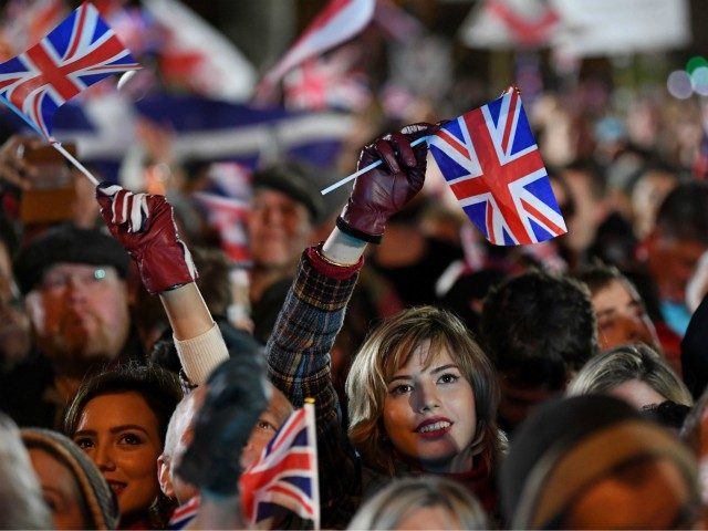 TOPSHOT - Brexit supporters wave Union flags as the time nears 11 O'Clock, in Parliament Square, venue for the Leave Means Leave Brexit Celebration in central London on January 31, 2020, the moment that the UK formally leaves the European Union. - Brexit supporters gathered outside parliament on Friday to …
