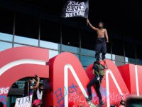 ATLANTA, GA - MAY 29: A man waves a Black Lives Matter flag atop the CNN logo during a protest in response to the police killing of George Floyd outside the CNN Center on May 29, 2020 in Atlanta, Georgia. Demonstrations are being held across the U.S. after George Floyd …