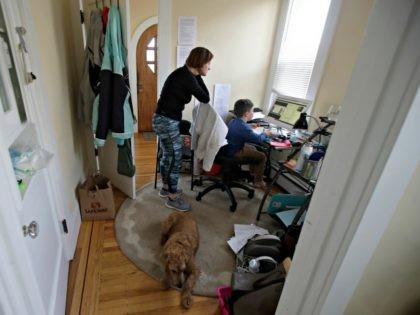 In this Thursday, March 19, 2020, photo, Rebecca Biernat watches as her son Seamus Keenan, 6, takes a live class online at their home in San Francisco. At bottom is their dog, Rosie. California's Bay Area has been shut down for more than a week, the first region of America …