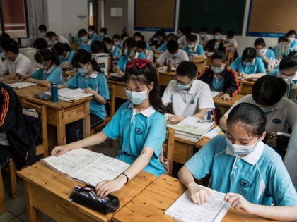 Students wear face masks as they study in a classroom in a high school in Wuhan in China's central Hubei province on July 10, 2020. - High schools in Wuhan reopened on July 10 after the start of the term was delayed due to the COVID-19 coronavirus outbreak. (Photo by …