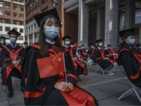 BEIJING, CHINA - JUNE 30: A Chinese student from Renmin University of China holds a flag as she sits with others as they are seated to adhere to social distancing during their graduation ceremony at the school's campus on June 30, 2020 in Beijing, China. Renmin University, also known as …