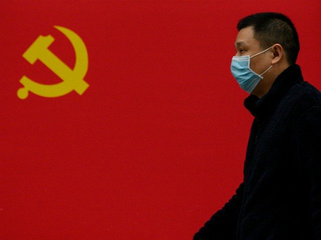 A man wearing a face mask as a preventive measure against the COVID-19 coronavirus walks past a Communist Party flag along a street in Wuhan in China's central Hubei province on March 31, 2020. (Photo by NOEL CELIS / AFP) (Photo by NOEL CELIS/AFP via Getty Images)