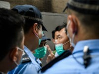 Police interrupt a march by a group of pro-democracy protesters (C), before issuing them with fines for breaking government-imposed social distancing rules against the COVID-19 coronavirus, during their route from outside the Western Police Station to the Chinese Liaison Office in Hong Kong on May 22, 2020. - A proposal …
