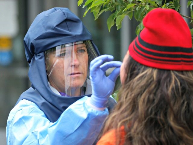 In this May 14, 2020, photo, Salt Lake County Health Department public health nurse Lee Cherie Booth performs a COVID-19 test outside the Salt Lake County health department, in Salt Lake City. People who test positive are logged into an online database and assigned as new case to contract tracers …