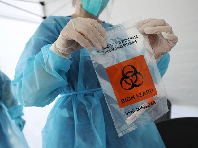 LOS ANGELES, CALIFORNIA - JULY 15: A nurse seals a specimen bag containing a COVID-19 test swab at a St. John's Well Child & Family Center mobile clinic set up outside Walker Temple AME Church in South Los Angeles amid the coronavirus pandemic on July 15, 2020 in Los Angeles, …