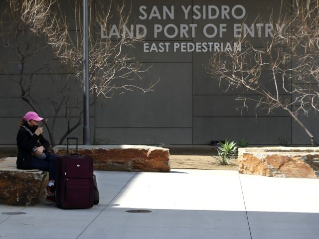 SAN DIEGO, CALIFORNIA - MARCH 21: A traveler sits down outside the U.S. Customs and Border Protection - San Ysidro Port of Entry on March 21, 2020 in San Diego, California. The United States and Mexico announced a temporary ban on non-essential and leisure travel across the U.S. - Mexican …