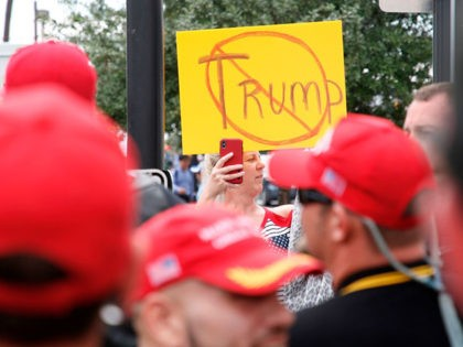 """An anti-Trump demonstrator holds up a placard and films a group of supporters of US President Donald Trump, wearing """"Make America Great Again"""" hats, near the Amway Center on June 18, 2019, Orlando, Florida. - President Trump is expected to launch his 2020 re-election campaign in Orlando, June 18. (Photo …"""