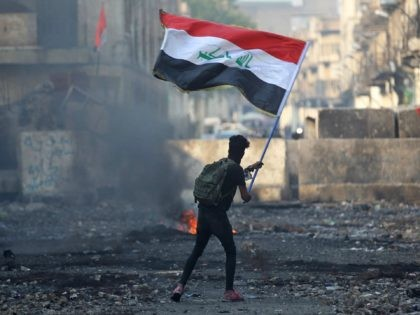 An Iraqi anti-government protester waves a national flag close to a concrete barricade amidst clashes with security forces along the capital Baghdad's Rasheed street near al-Ahrar bridge on November 29, 2019. - Iraq's embattled premier announced on November 29 he will resign in keeping with the wishes of the country's …