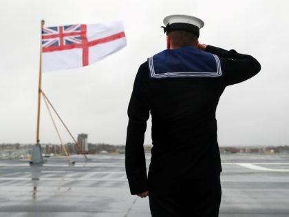 Members of the ship's company raise the White Ensign on the stern of the Royal Navy aircraft carrier, HMS Prince of Wales, during her commissioning ceremony at Portsmouth Naval Base, south England on December 10, 2019. (Photo by Andrew Matthews / POOL / AFP) (Photo by ANDREW MATTHEWS/POOL/AFP via Getty …