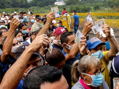 "People coming from Venezuela with protective face masks as a precautionary measure to avoid contracting the new coronavirus, COVID-19, show hold their documents on the border at Simon Bolivar International Bridge, in Cucuta, Colombia, on March 12, 2020. - Colombia declared on March 12, 2020 a ""Health Emergency"" due to …"
