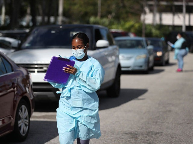 WEST PALM BEACH, FLORIDA - MARCH 16: Health care staff from the FoundCare center wear protective gear as they help people who called to setup a drive through appointments to be tested for the coronavirus in the centers parking lot on March 16, 2020 in West Palm Beach, Florida. FoundCare, …