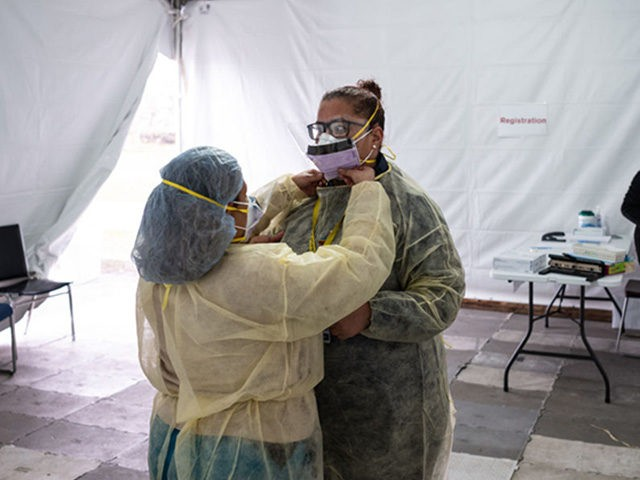 NEW YORK, NY - MARCH 20: Nurses adjust protective masks inside a testing tent at St. Barnabas hospital on March 20, 2020 in New York City. St. Barnabas hospital in the Bronx set-up tents to triage possible COVID-19 patients outside before they enter the main Emergency department area. (Photo by …