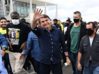 Brazil's President Jair Bolsonaro greets supporters upon arrival at Planalto Palace in Brasilia, on May 24, 2020, amid the COVID-19 coronavirus pandemic. - Despite positive signs elsewhere, the disease continued its surge in large parts of South America, with the death toll in Brazil passing 22,000 and infections topping 347,000, …