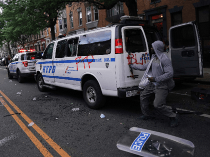 A man loots an NYPD police van during a demonstration against the killing of George Floyd by Minneapolis police on Memorial Day on May 30, 2020 in the Borough of Brooklyn in New York. - Demonstrations are being held across the US after George Floyd died in police custody on …