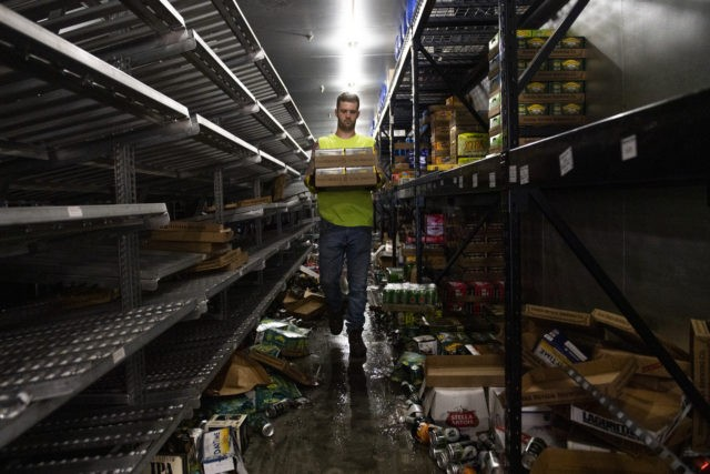 MINNEAPOLIS, MN - JUNE 05: A worker removes cases of beer from the cooler inside Chicago Lake Liquors after it was looted during the protests and riots which followed the death of George Floyd on June 5, 2020 in Minneapolis, Minnesota. All of the merchandise left in the store will …