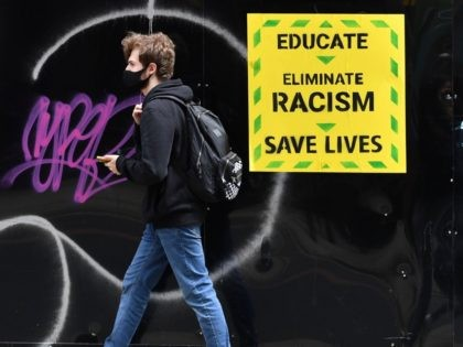 Pedestrians wearing PPE (personal protective equipment), including a face mask as a precautionary measure against COVID-19, walk past an anti-racism poster in the them of the British government's Coronavirus slogan, near a demonstration in Manchester, northern England, on June 6, 2020, to show solidarity with the Black Lives Matter movement …