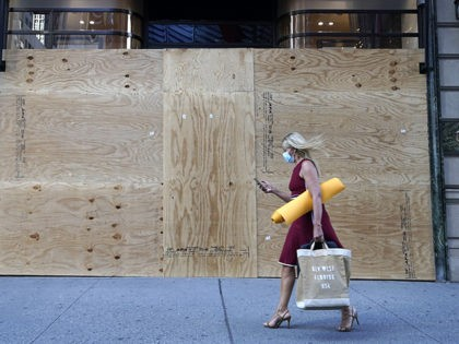 "TOPSHOT - A woman walks by a boarded up Cartier store on 5th Avenue in New York City June 8, 2020. - Today New York City enters ""Phase 1"" of a four-part reopening plan after spending more than two months under lockdown. New York City is the final region in …"