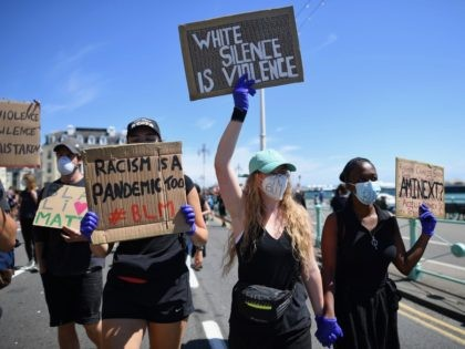 Protesters hold up placards as they march along the seafront in support of the Black Lives Matter movement at a protest action in Brighton, on the south coast of England on June 13, 2020, in the aftermath of the death of unarmed black man George Floyd in police custody in …