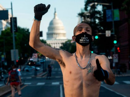 "A Black Lives Matter protester wearing a ""I Can't Breate"" mask raises his fist during a demonstration near the US Capitol in Washington, DC on June 24, 2020. (Photo by ANDREW CABALLERO-REYNOLDS / AFP) (Photo by ANDREW CABALLERO-REYNOLDS/AFP via Getty Images)"