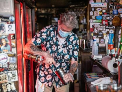 A bartender wearing a facemask makes a drink at a restaurant in Austin, Texas, June 26, 2020. - Texas Governor Greg Abbott ordered bars to be closed by noon on June 26 and for restaurants to be reduced to 50% occupancy. Coronavirus cases in Texas have spiked in recent weeks …