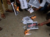 Members of the City Youth Organisation burn posters with the logos of Chinese apps in support of the Indian government for banning the wildly popular video-sharing 'Tik Tok' app, in Hyderabad on June 30, 2020. - TikTok on June 30 denied sharing information on Indian users with the Chinese government, …