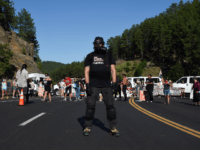 Activists and members of different tribes from the region block the road to Mount Rushmore National Monument with vans as they protest and confront police and military personnel in Keystone, South Dakota on July 3, 2020, during a demonstration around the Mount Rushmore National Monument and the visit of US …