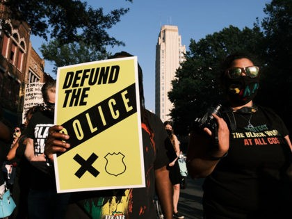 "RICHMOND, VA - JULY 03: A protester carries a sign that reads ""Defund The Police"" during the Black Women Matter ""Say Her Name"" march on July 3, 2020 in Richmond, Virginia. Protests continue around the country after the death of African Americans while in police custody. (Photo by Eze Amos/Getty …"