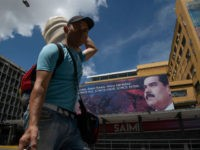 CARACAS, VENEZUELA - JULY 06: A man wearing a face mask walks in front of an image of Venezuela's president Nicolas Maduro in Downtown Caracas on July 6, 2020 in Caracas, Venezuela. Venezuela resumes today a total lockdown after a week of easing measures. The country will apply a so-called …