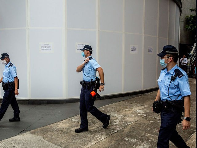 Police walk past windows that have been covered up at the Metro Park hotel in Causeway Bay on July 7, 2020, the hotel which is being retrofitted and turned into office for safeguarding national security of the peoples republic of China in the Hong Kong special administrative region. - China …