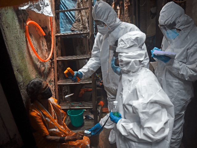 Medical volunteers wearing Personal Protective Equipment (PPE) gear take temperature reading of a woman as they conduct a door-to-door medical screening inside Dharavi slums to fight against the spread of the COVID-19 coronavirus, in Mumbai on July 9, 2020. - India's major cities have been worst hit by the pandemic. …
