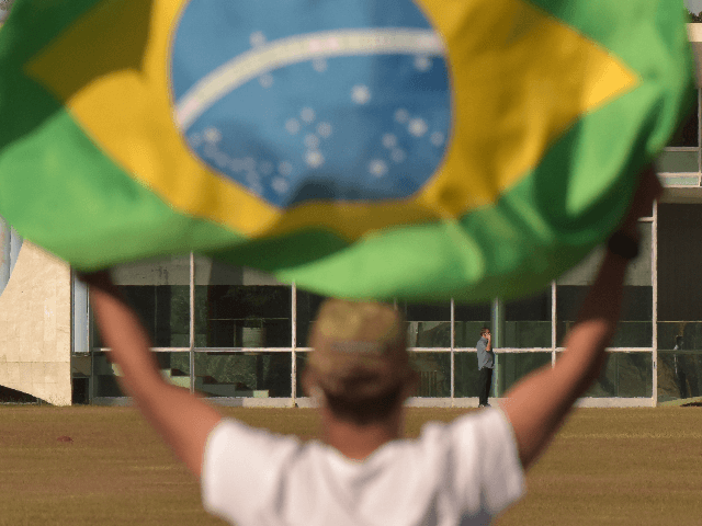 Supporter of Brazilian President Jair Bolsonaro waves him at the door of official residence after testing positive of coronavirus (COVID-19) amidst the coronavirus pandemic in Alvorada Palace on July 09, 2020 in Brasilia. President Bolsonaro announced Tuesday he tested positive for COVID-19 after presenting symptoms. Brazil has over 1.713,000 confirmed positive …
