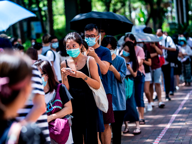 A woman (centre L) uses her phone while waiting to vote during primary elections in Hong Kong on July 12, 2020. - Pro-democracy parties in Hong Kong held primary polls on July 11 and 12 to choose candidates for upcoming legislative elections despite warnings from government officials that it may …