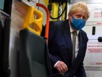 Britain's Prime Minister Boris Johnson, wearing a face mask or covering due to the COVID-19 pandemic, boards an ambulance to talk with a paramedic, during his visit to the headquarters of the London Ambulance Service NHS Trust in central London on July 13, 2020. (Photo by Ben STANSALL / various …