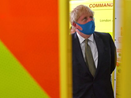 LONDON, UNITED KINGDOM - JULY 13: Britain's Prime Minister Boris Johnson, wearing a face mask or covering due to the COVID-19 pandemic, talks with a paramedic standing in side an ambulance, during his visit to the headquarters of the London Ambulance Service NHS Trust on July 13, 2020 in London, …