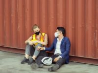 Young worker and engineer sitting failed and stressed at cargo container