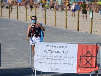 A woman leaves the beach as a sign on a fence informs people of the closure of the beach due to reaching the allowed capacity, in Barcelona on July 19, 2020. (Photo by Josep LAGO / AFP) (Photo by JOSEP LAGO/AFP via Getty Images)