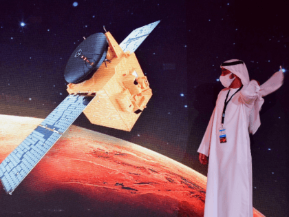 "An Emirati walks past a screen displaying the ""Hope"" Mars probe at the Mohammed Bin Rashid Space Centre in Dubai on July 19, 2020, ahead of it's expected launch from Japan. - The probe is one of three racing to the Red Planet, with Chinese and US rockets also taking …"