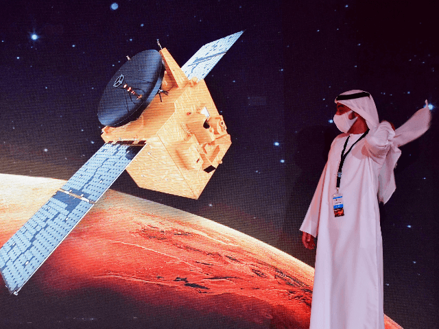"""An Emirati walks past a screen displaying the """"Hope"""" Mars probe at the Mohammed Bin Rashid Space Centre in Dubai on July 19, 2020, ahead of it's expected launch from Japan. - The probe is one of three racing to the Red Planet, with Chinese and US rockets also taking …"""